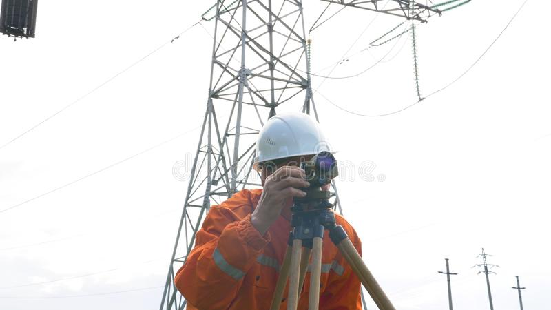 Skilled surveyor works with dumpy level rotating knob stock photography