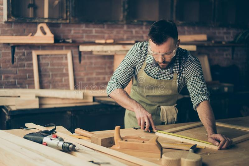 Skilled talented bearded busy confident bearded handyman clothed. In checkered casual shirt apron protective glasses is measuring the wooden frame`s length on stock photography