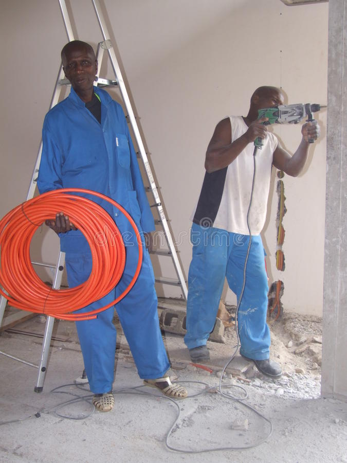 SKILLED WORKERS. Image of highly skilled African workers in their work clothes and work tools in their hand taking a bigger picture at work royalty free stock images