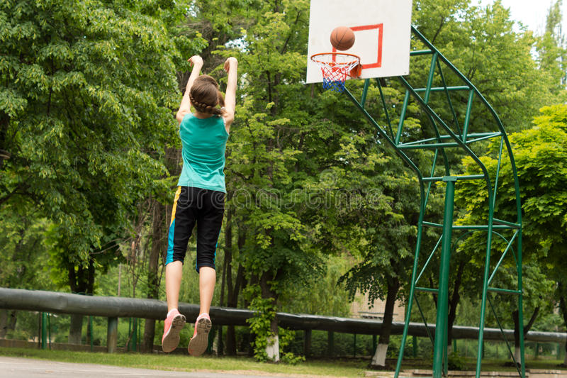Skilled young basketball player shooting a goal. Skilled athletic young female basketball player shooting a goal on an outdoor court jumping in the air as she stock photos
