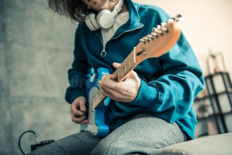 Skilled young man in blue sweatshirt showing his qualification. Playing at home. Skilled young man in blue sweatshirt showing his qualification while performing royalty free stock photo