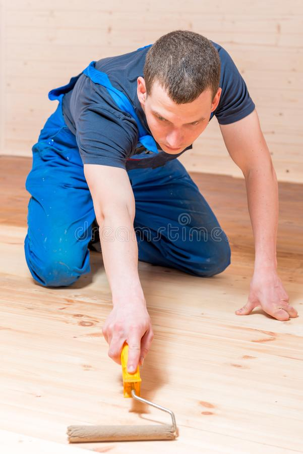 Skilled young worker paint roller on a wooden floor stock photography