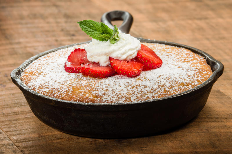 Skillet baked yellow cake with berries. Skillet baked yellow cake with cream and red strawberries stock photography