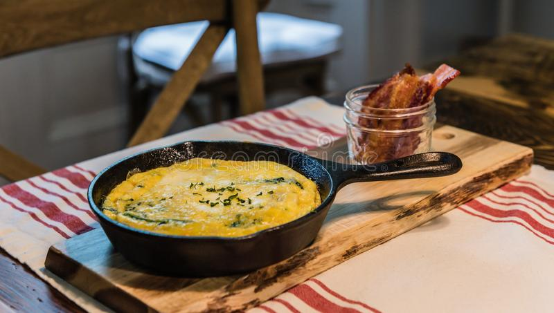 Skillet Omelette and Bacon On Wood Plank. Savory omelette presented in iron skillet and bacon served upright in mason jar stock image