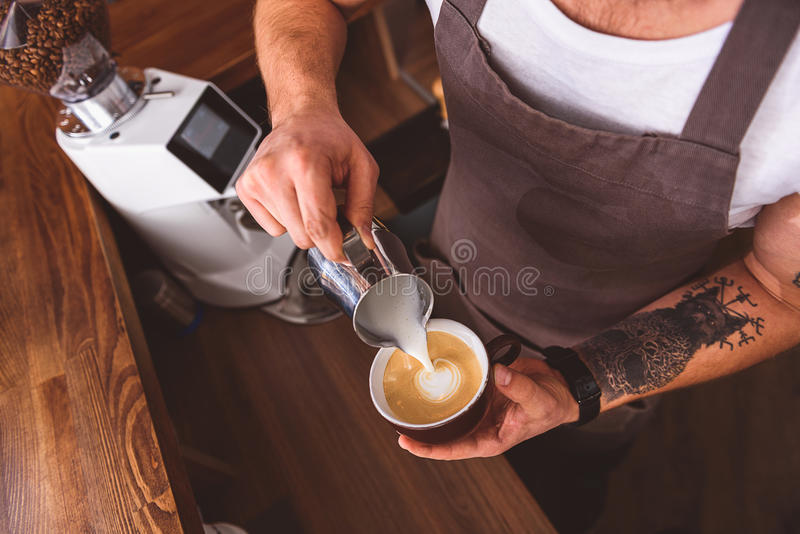 Skillful bartender working in coffeehouse royalty free stock photography