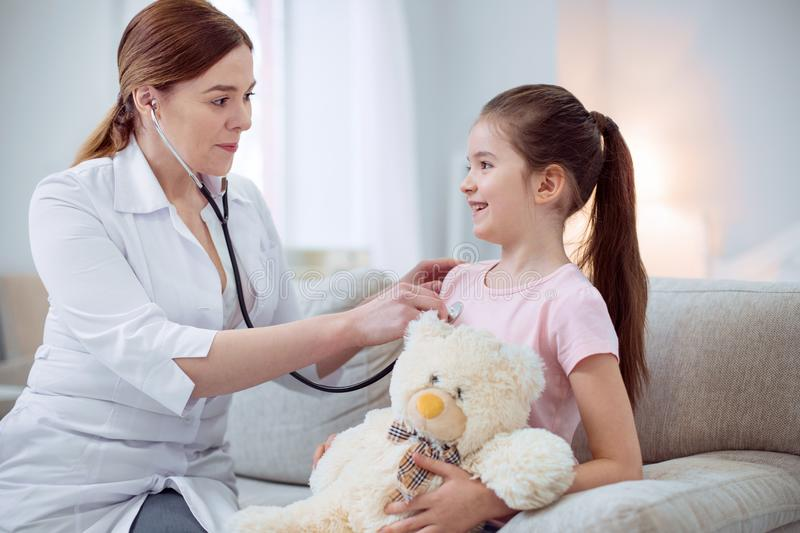 Skillful female doctor checking heart beat royalty free stock images
