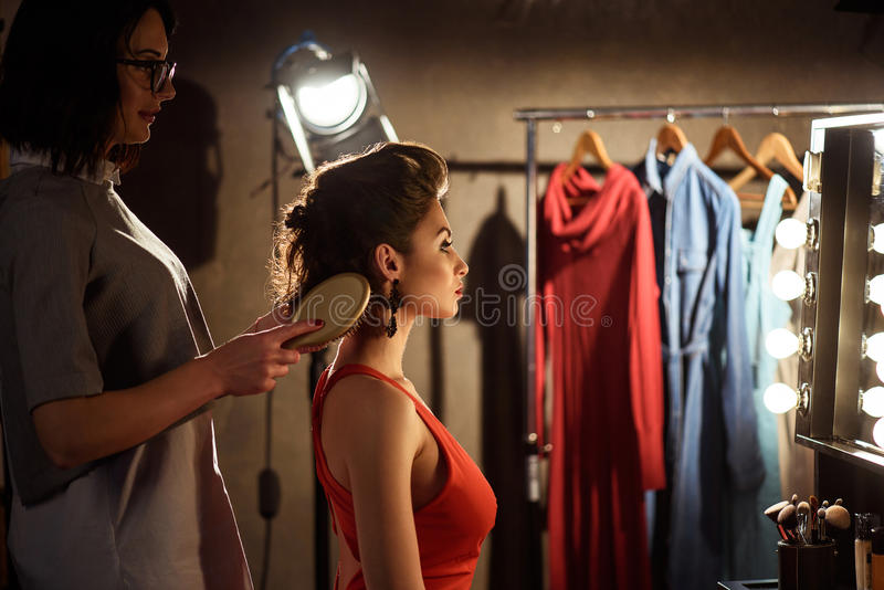 Skillful stylist making hairstyle backstage royalty free stock image