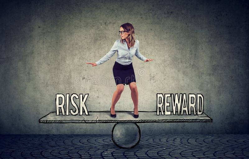 Skillful young business woman balancing between reward and risk. In challenging corporate environment royalty free stock images