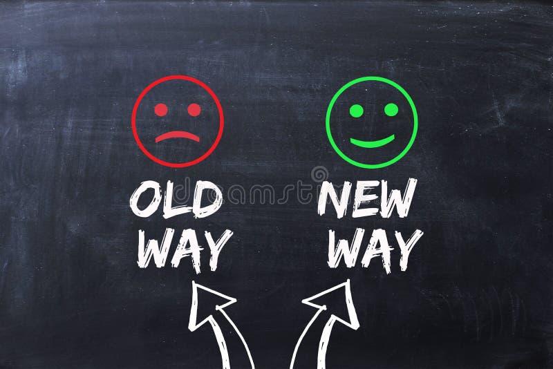 Skillnad mellan den gamla vägen och nya vägen som illustreras med lyckliga och ledsna framsidor på den svart tavlan royaltyfri fotografi