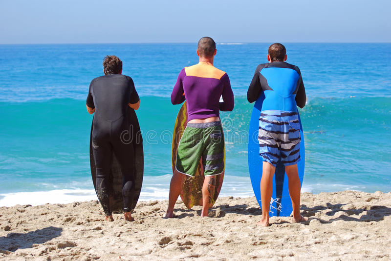 Skim Boarders wait for a wave to ride at Aliso Beach in Laguna Beach, California. Image shows skim boarders waiting for a shore break wave to ride at Aliso royalty free stock images