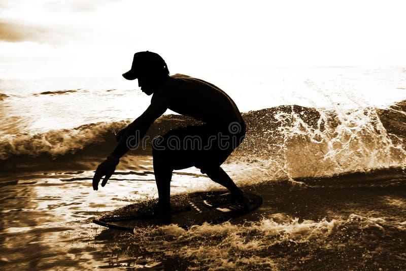 Skimboarder em gotas da água fotos de stock