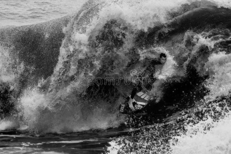 Skimboarder saute sur une vague photos stock