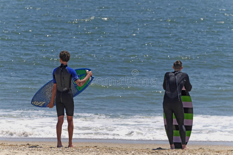 Skimboarders Waiting for Wave. Skimboarders in wetsuits examine waves prior to the 2014 Southside Shootout 2014 skimboard competion at Delaware Seashore State stock photo