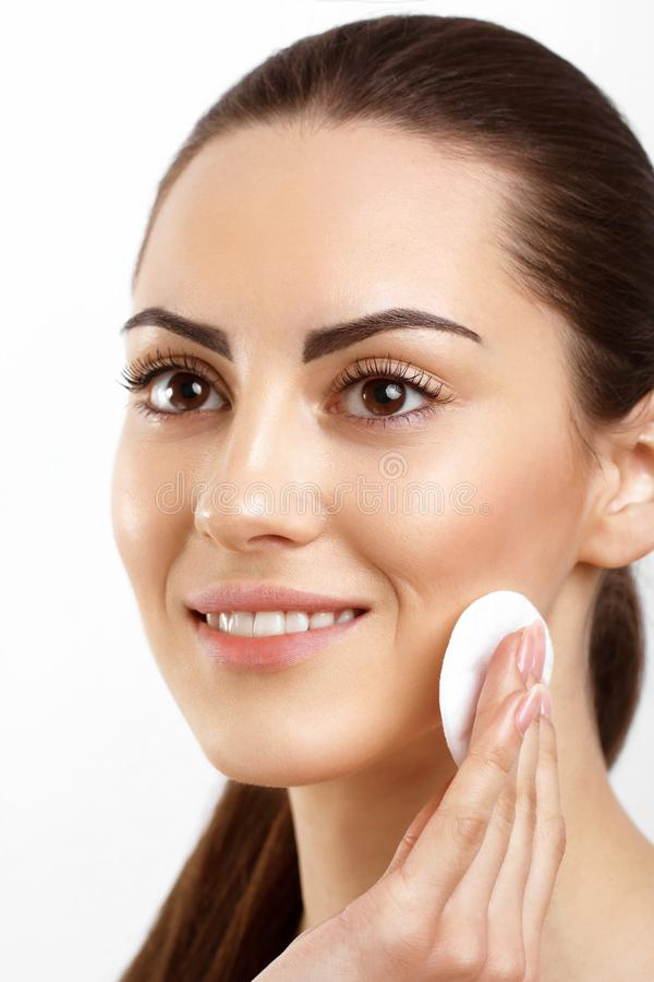 Skin Care. Beautiful Happy Woman Removing Face Makeup Using Cotton Pad. Closeup. Portrait Of Woman Smiling   With Natural Makeup. Touching Perfect Fresh Soft stock photos