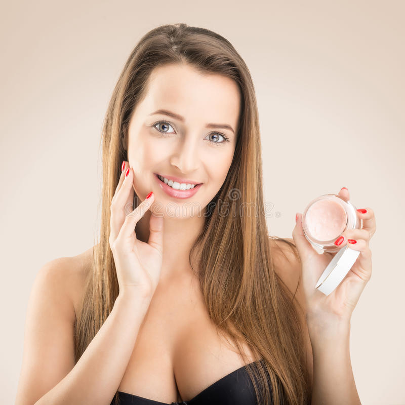 Skin Care - Beautiful woman with face cream stock photography