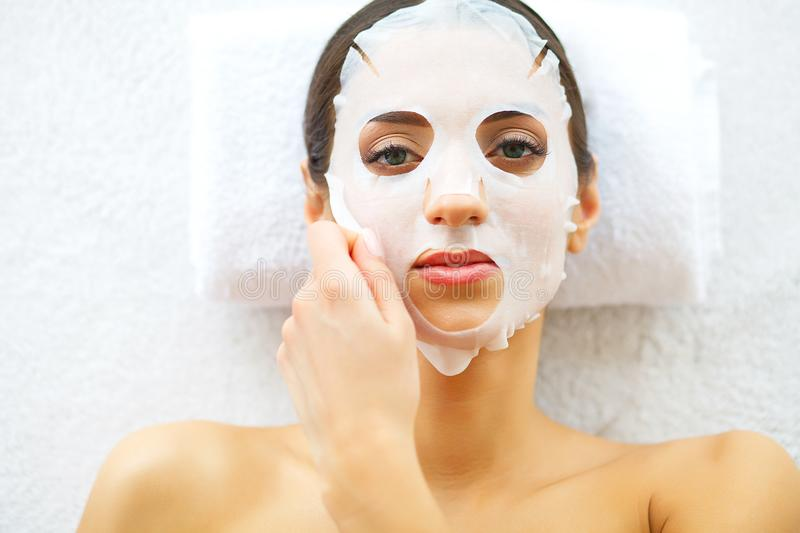 Skin and care. Beautiful Woman Lying With Face Mask. Pure and Beautiful Skin. Young Woman Makes a Face Mask. Caring for Salon. ?ig. H Rezolution stock photography