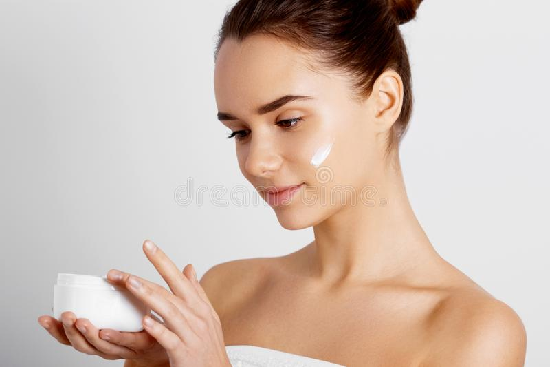 Skin care. Beauty Concept. Young pretty woman holding cosmetic cream.Model Girl With Natural Nude Makeup, stock photo