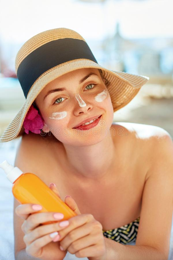 Skin care. Beauty Concept. Young pretty woman holding  sun cream and applying on her face. Female in hat smear  sunscreen lotion royalty free stock photography