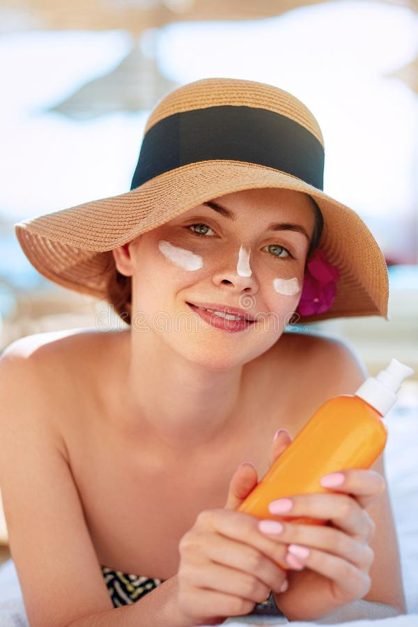 Skin care. Beauty Concept. Young pretty woman holding  sun cream and applying on her face. royalty free stock photos