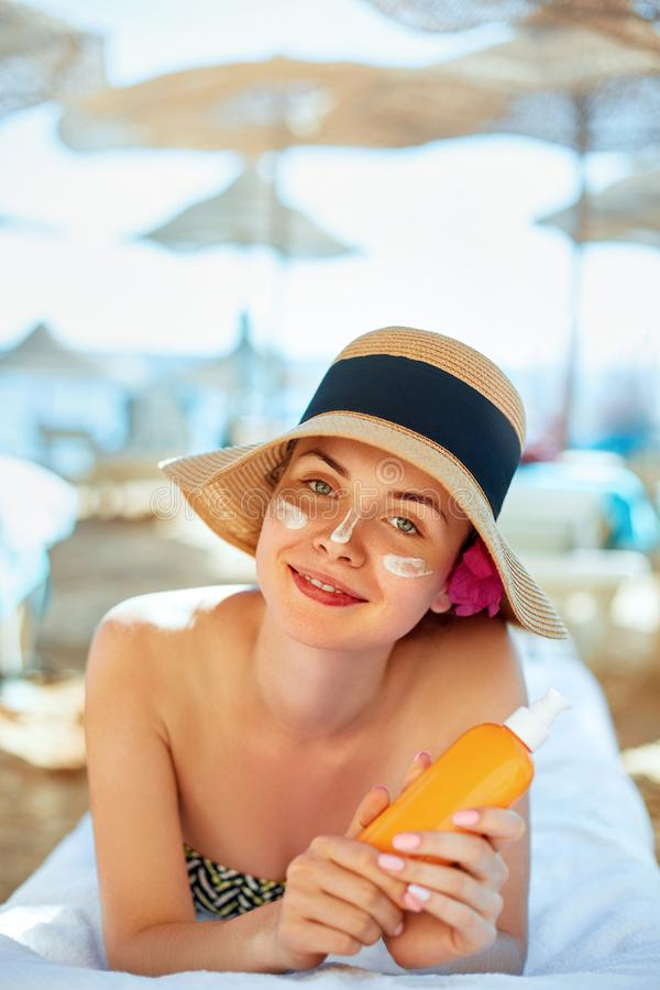 Skin care. Beauty Concept. Young pretty woman holding sun cream and applying on her face stock photos