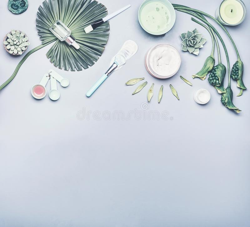 Skin care cosmetic and facial sheet mask. Various cosmetics product: serum, cream and gel with tropical leaves and flowers. On gray background, top view royalty free stock photos