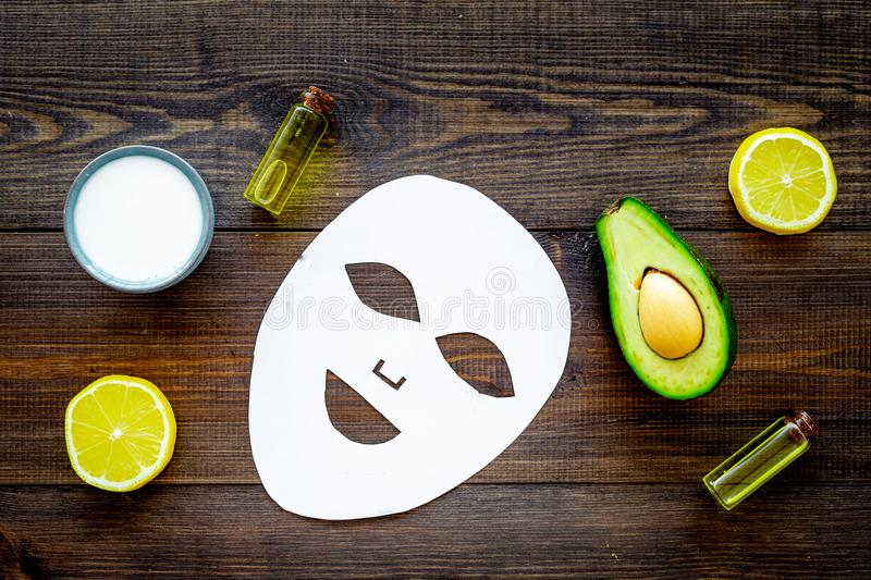 Skin care. Facial mask, cream and lotion based on avocado and lemon essential oil on dark wooden background top view royalty free stock photos