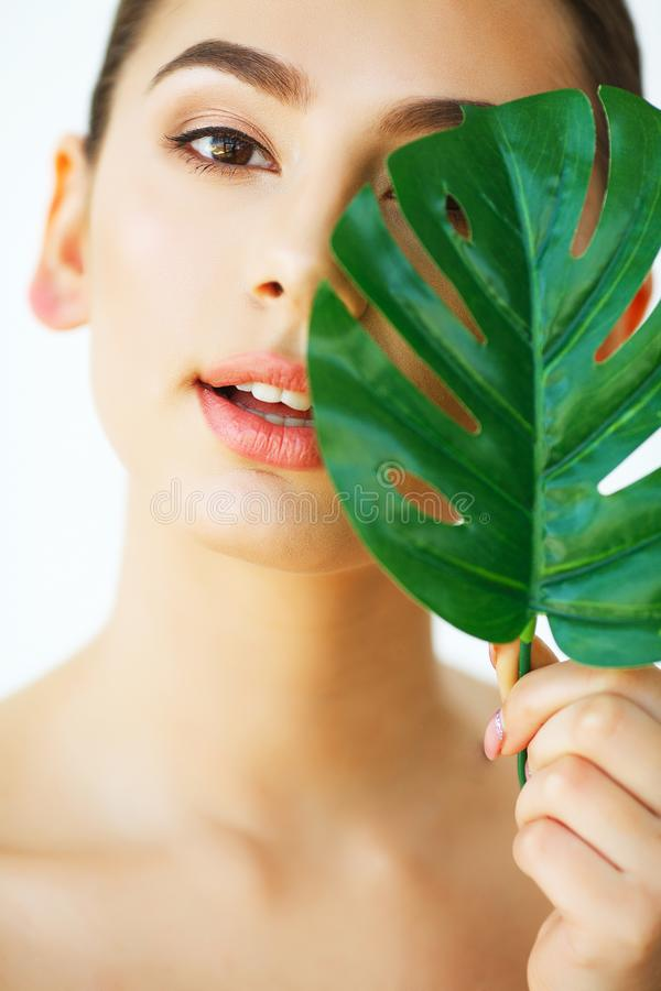 Skin Care. Green Leaf Shading a Half of Beautiful Woman Face. Be stock photos
