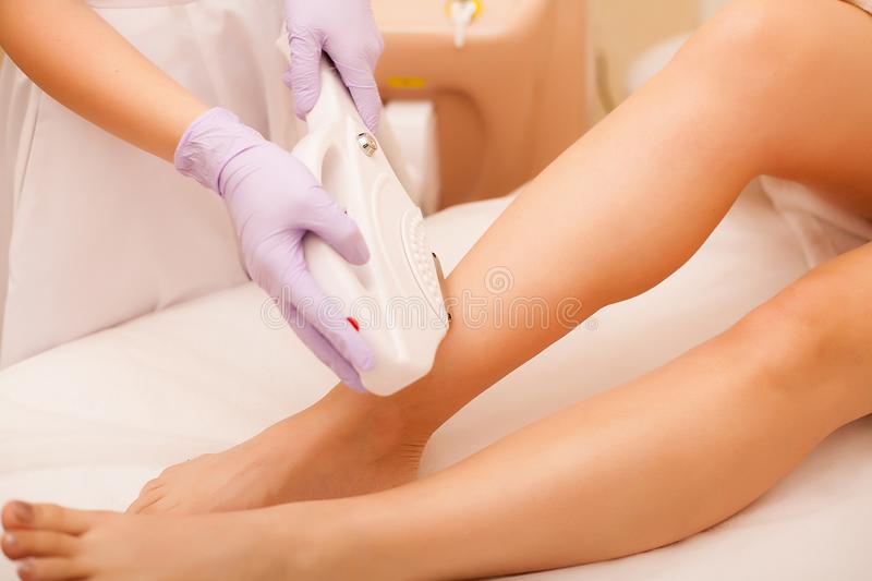 Skin Care. Hair removal on the legs, laser procedure at clinic. Beautician removes hair on beautiful female legs using a. Laser royalty free stock images