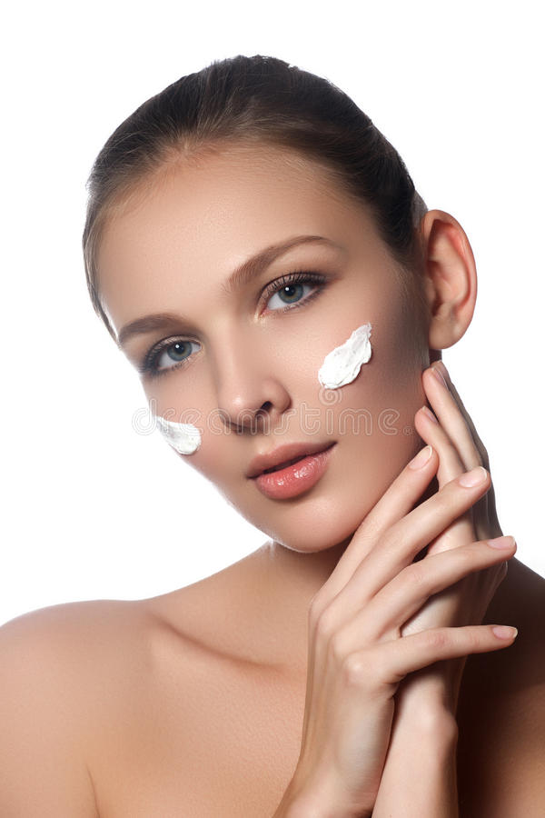Skin care lady putting face cream. Attractive brunette girl royalty free stock photography