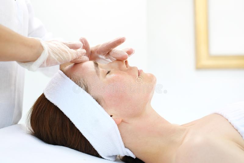 Skin care, massage the facial skin. Female beautician, massage your face. Skin care of the neck and cleavage. Massage in the beauty salon stock photography