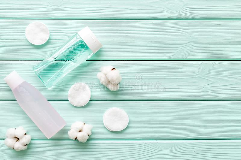 Skin care cosmetics with facial tonic, mycelial water and cotton pads on mint green wooden background top view mockup stock photo