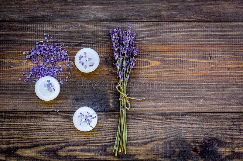 Skin care and relax. Cosmetics and aromatherapy concept. Lavender spa salt and candles on dark wooden background top. View stock images