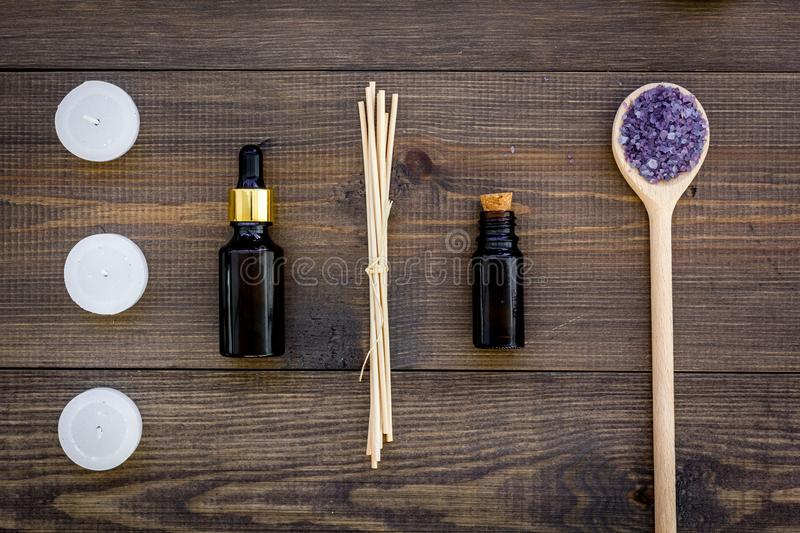 Skin care and relax. Cosmetics and aromatherapy concept. Lavender spa salt and oil on dark wooden background top view.  stock photo