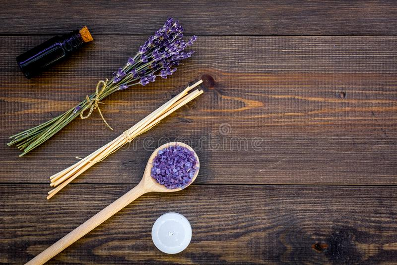 Skin care and relax. Cosmetics and aromatherapy concept. Lavender spa salt and oil on dark wooden background top view.  stock images
