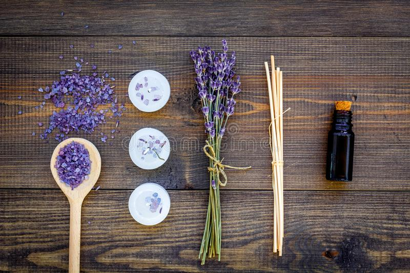 Skin care and relax. Cosmetics and aromatherapy concept. Lavender spa salt and oil on dark wooden background top view royalty free stock photos