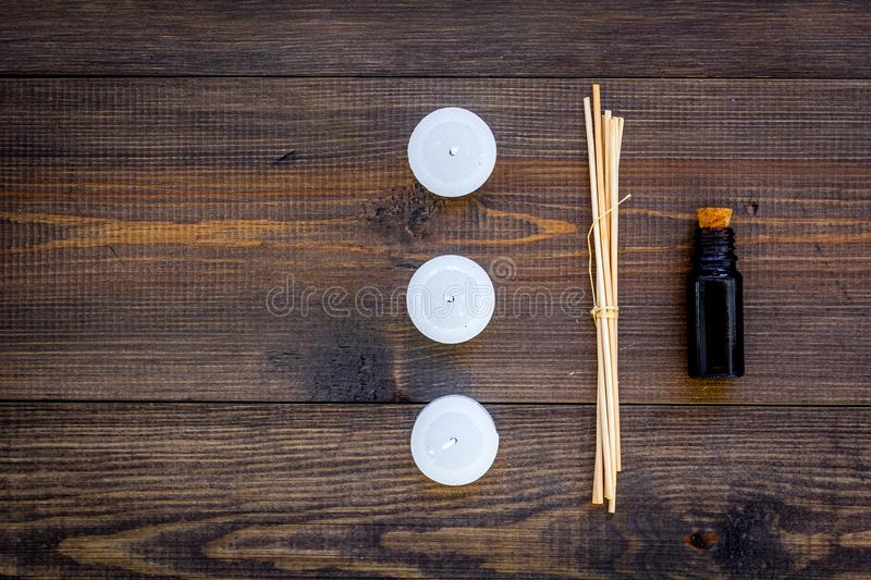 Skin care and relax. Cosmetics and aromatherapy concept. Oil and candles on dark wooden background top view copyspace. Skin care and relax. Cosmetics and royalty free stock photo
