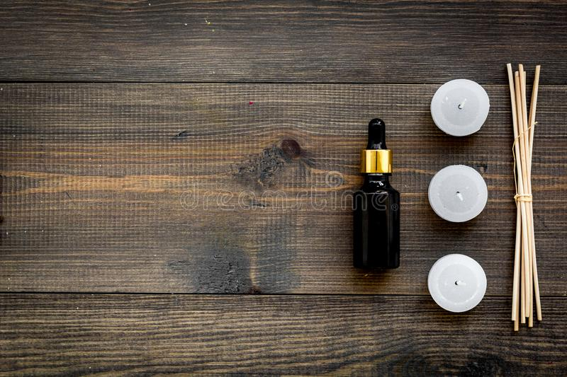 Skin care and relax. Cosmetics and aromatherapy concept. Oil and candles with spices cinnamon on dark wooden background. Top view royalty free stock image