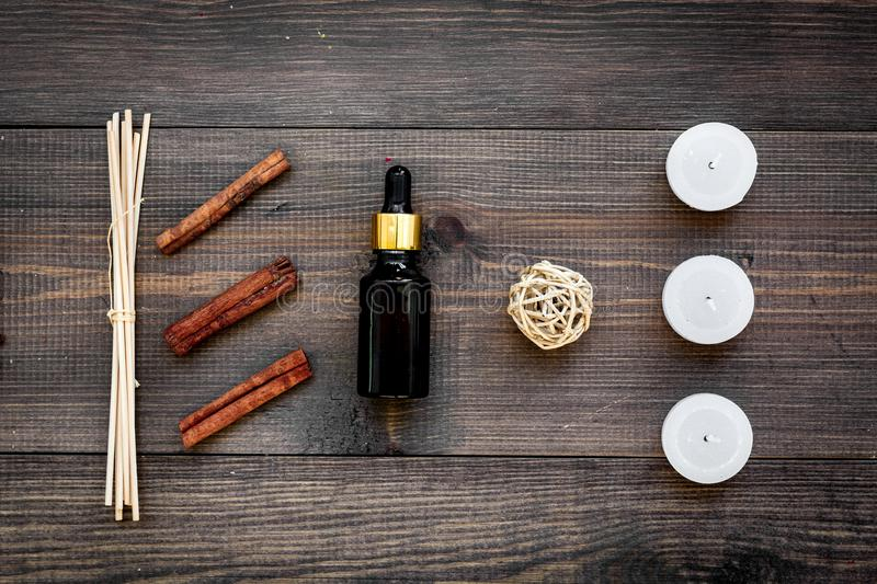 Skin care and relax. Cosmetics and aromatherapy concept. Oil and candles with spices cinnamon on dark wooden background. Top view stock images