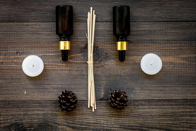 Skin care and relax. Cosmetics and aromatherapy concept. Pine oil on dark wooden background top view.  royalty free stock images