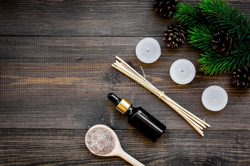 Skin care and relax. Cosmetics and aromatherapy concept. Pine spa salt and oil on dark wooden background top view.  royalty free stock photo