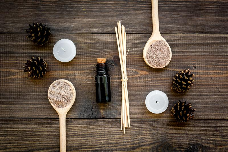 Skin care and relax. Cosmetics and aromatherapy concept. Pine spa salt and oil on dark wooden background top view.  royalty free stock photography