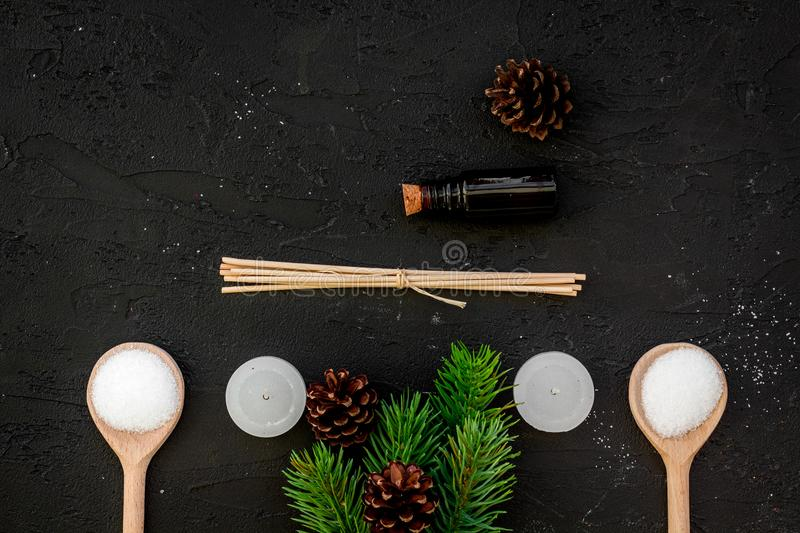 Skin care and relax. Cosmetics and aromatherapy concept. Pine spa salt, oil, spruce branch and pinecones on black. Background top view royalty free stock photo