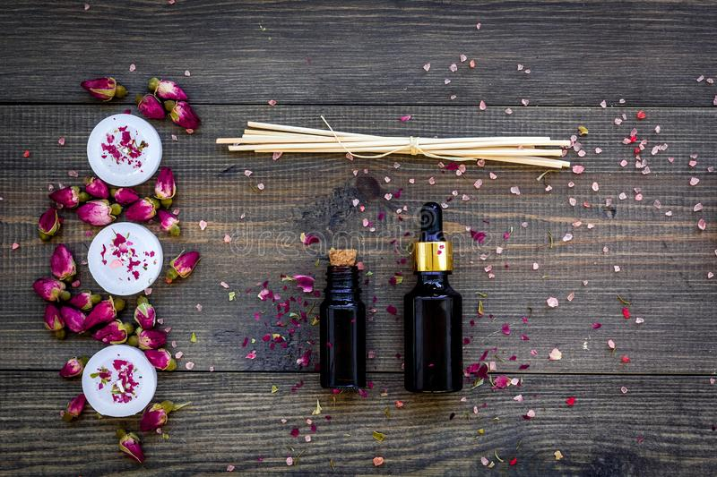 Skin care and relax. Cosmetics and aromatherapy concept. Rose oil and candles on dark wooden background top view stock photos