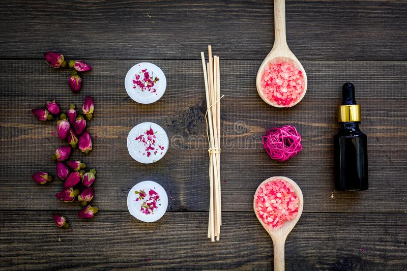 Skin care and relax. Cosmetics and aromatherapy concept. Rose spa salt and oil on dark wooden background top view.  stock image
