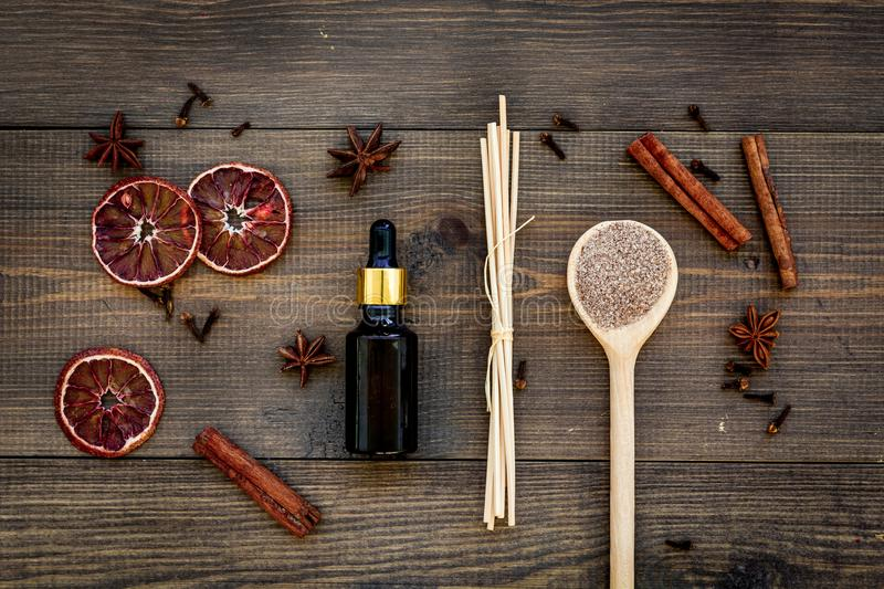 Skin care and relax. Cosmetics and aromatherapy concept. Spa salt and oil with spices cinnamon on dark wooden background. Top view royalty free stock images