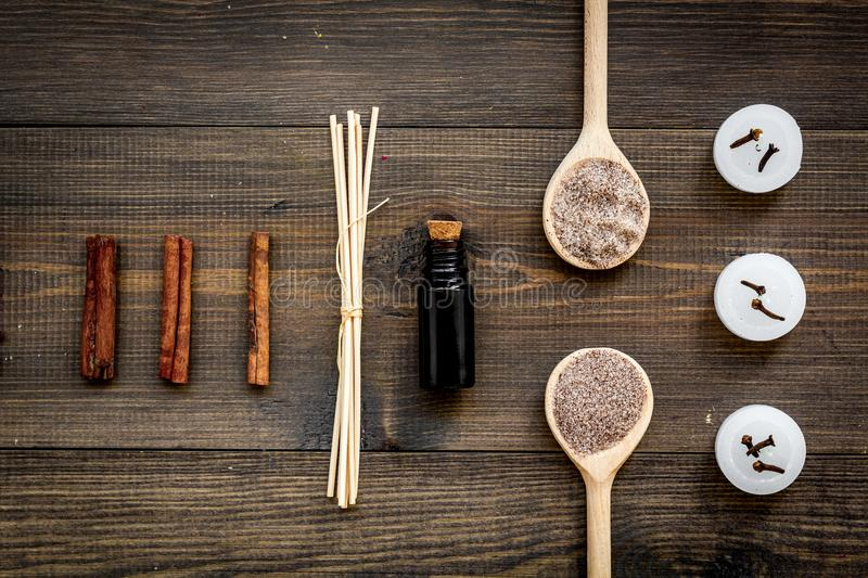 Skin care and relax. Cosmetics and aromatherapy concept. Spa salt and oil with spices cinnamon on dark wooden background stock photo