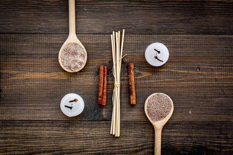 Skin care and relax. Cosmetics and aromatherapy concept. Spa salt with spices cinnamon on dark wooden background top. View royalty free stock photo