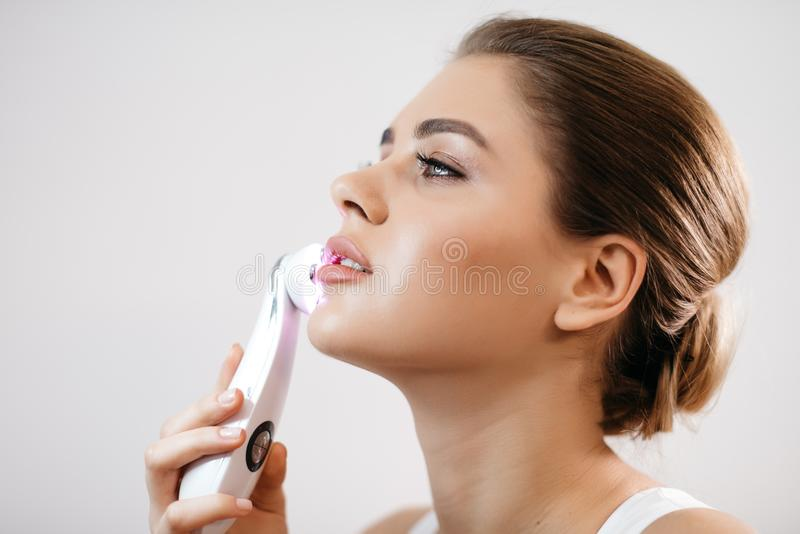 Skin Care. Side portrait of the charming healthy fresh woman with natural make-up using the electric facial massager at stock photos