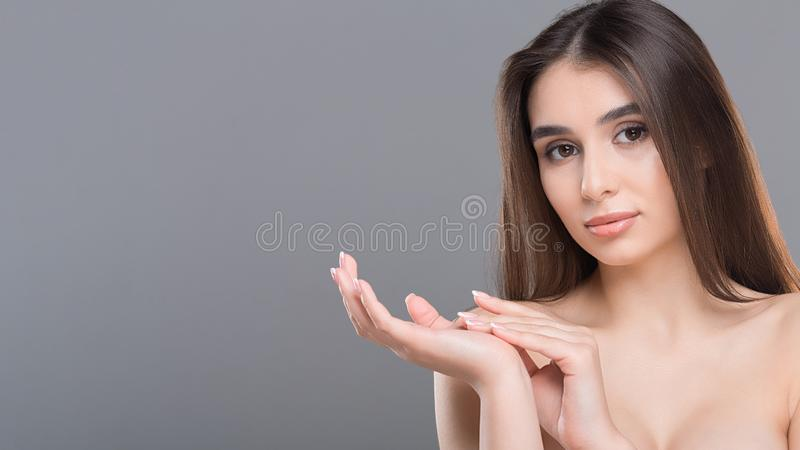 Young beautiful woman massaging her palms, grey background. Skin care and spa procedures for hands. Young beautiful woman massaging her palms, grey background royalty free stock photography