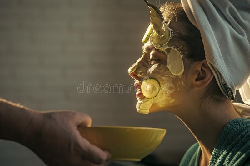 Skin care, spa, wellness. Beauty salon concept. Cosmetician hands with spoon and bowl. Rejuvenation, health, youth. Girl or woman get cucumber mask on face royalty free stock photos